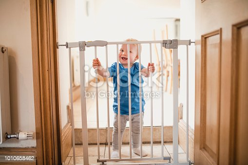 A joyful child smiles whilst holding on to a locked safety gate at home, he is wearing casual clothing and has a big grin on his face.