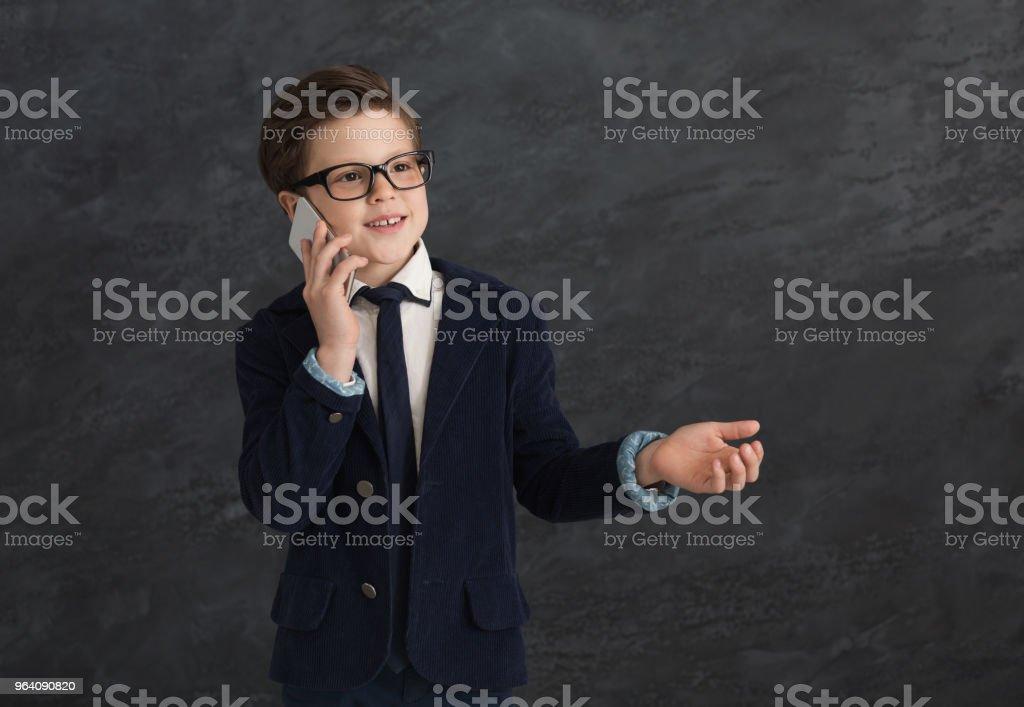 灰色の背景で携帯で話しているスーツの小さな男の子 - 1人のロイヤリティフリーストックフォト