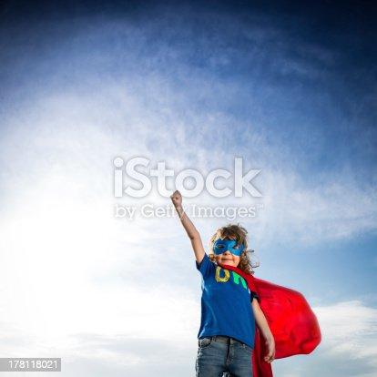 istock Small boy in superhero attire against blue sky 178118021