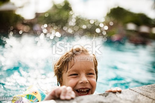 Portrait cute small boy splashing in the pool