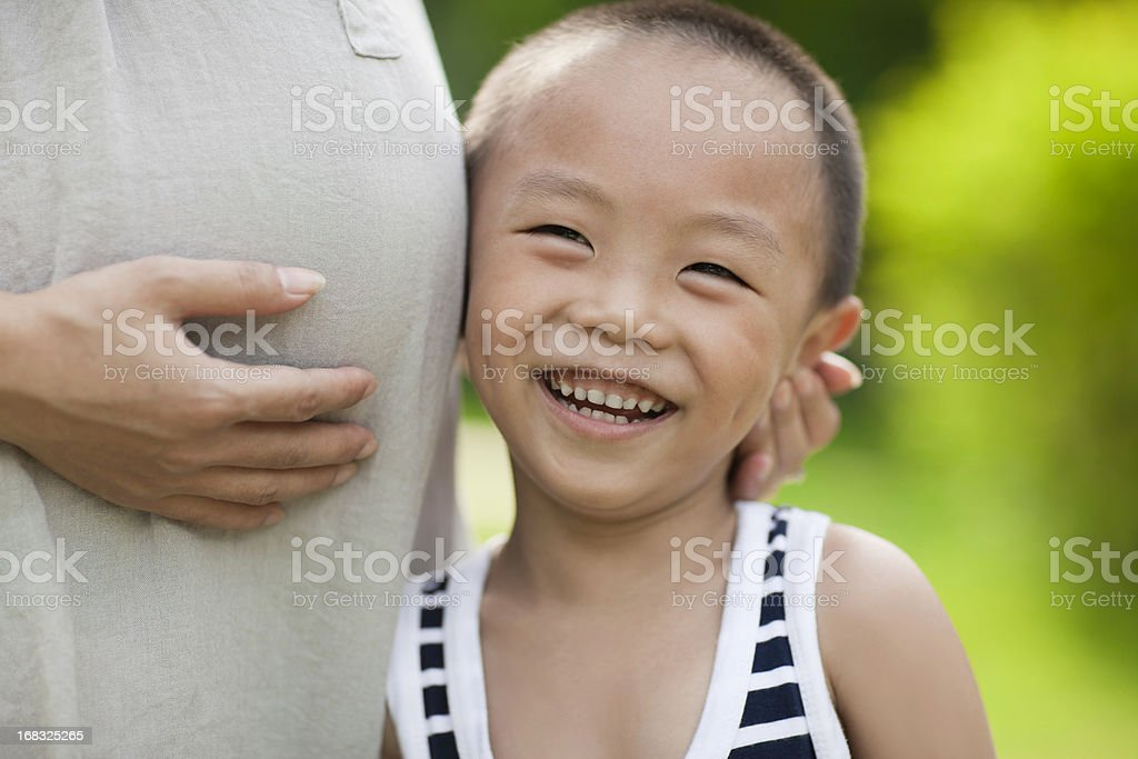 Small boy listening to mother's pregnant tummy royalty-free stock photo