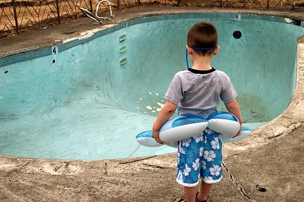 pequeno rapaz olhando para a piscina vazia - brinquedos na piscina imagens e fotografias de stock