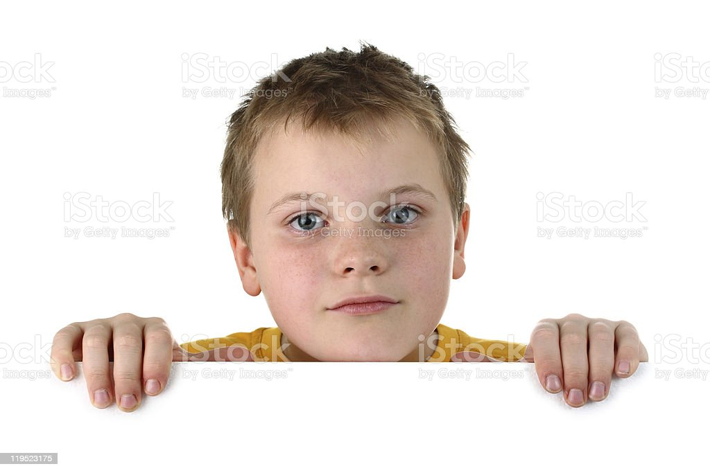 Small boy looking out of blank whiteboard isolated on white stock photo