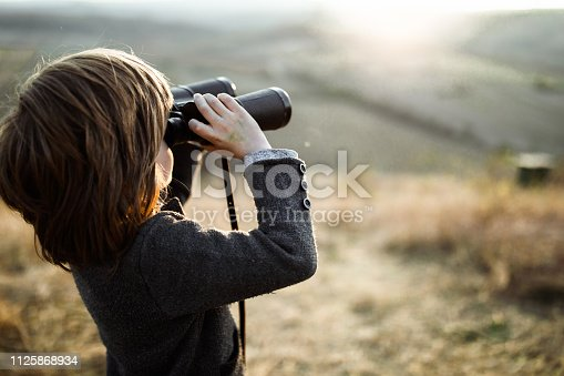 Little kid using binoculars while looking at view in autumn day. Copy space.