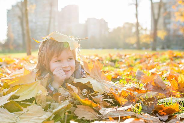 small boy lying among autumn leaves. - meerdere lagen effect stockfoto's en -beelden