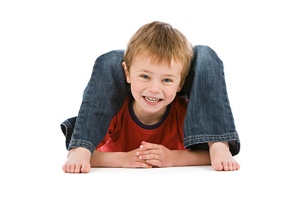 Small boy lying in impossibly bendy position stock photo