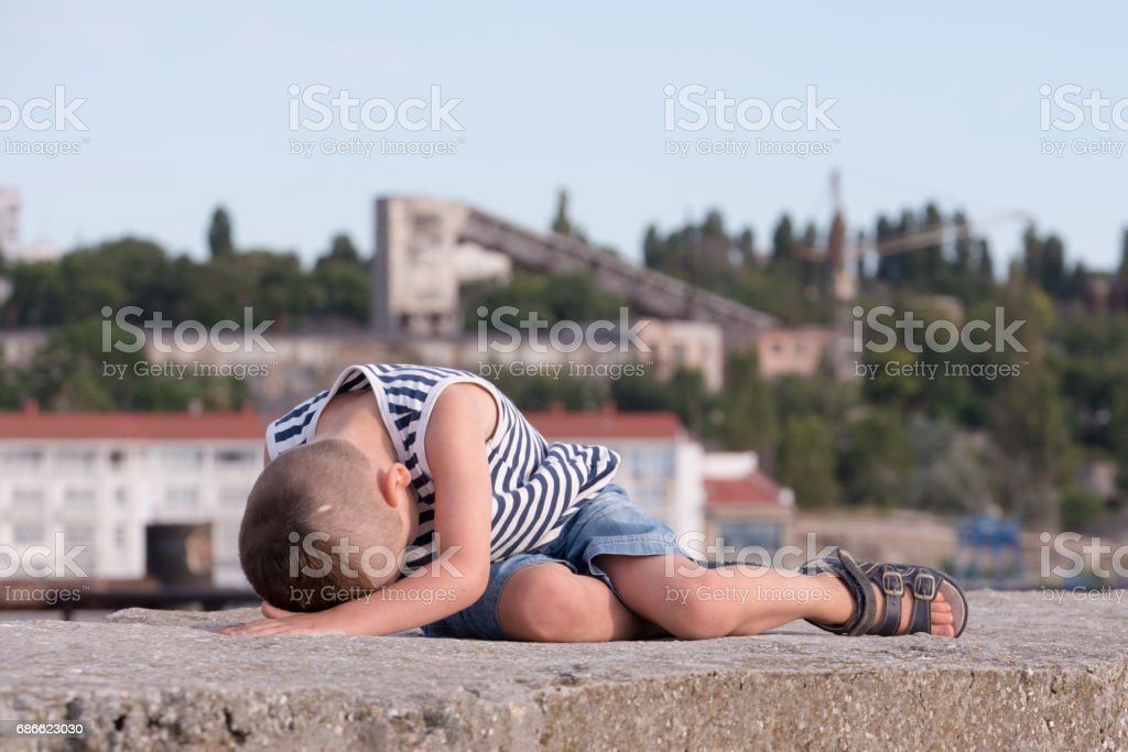 small boy lying on a background of port buildings and green trees royalty-free stock photo