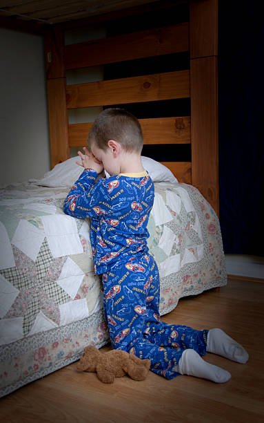 Small boy making his bedtime prayers stock photo