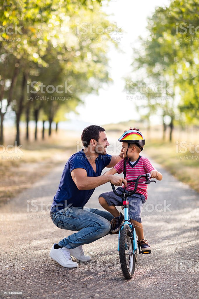 Small boy on bike enjoying day in nature with father. foto stock royalty-free