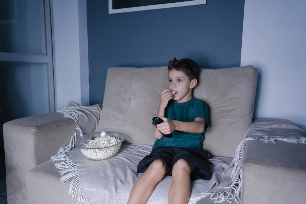 small boy on the couch watching tv and eating popcorn at night in the living room - tv e familia e ecrã imagens e fotografias de stock