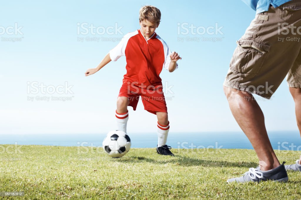 Small boy playing a soccer game with his father royalty-free stock photo