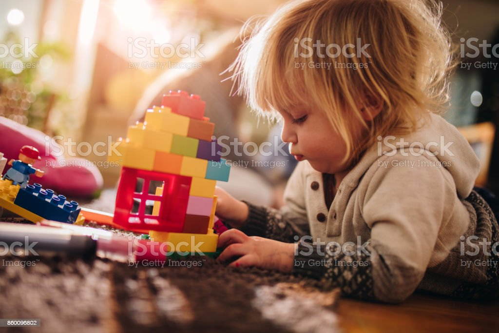 Small boy playing with plastic blocks on the floor. stock photo