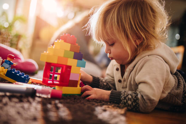 small boy playing with plastic blocks on the floor. - toy stock pictures, royalty-free photos & images