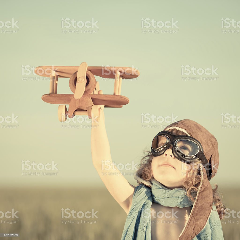 Small boy playing with wooden toy airplane stock photo