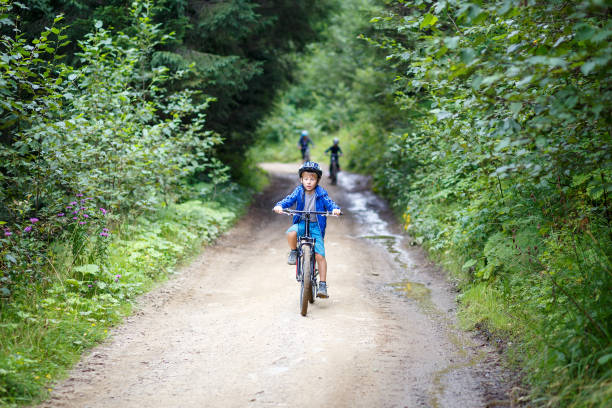 Small boy riding the bicycle on mountain road Small boy in helmet riding the bicycle on mountain road sergionicr stock pictures, royalty-free photos & images