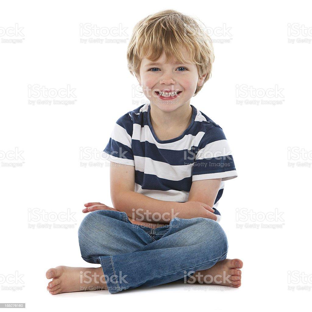 Petit garçon assis à pattes croisées souriant sur blanc - Photo