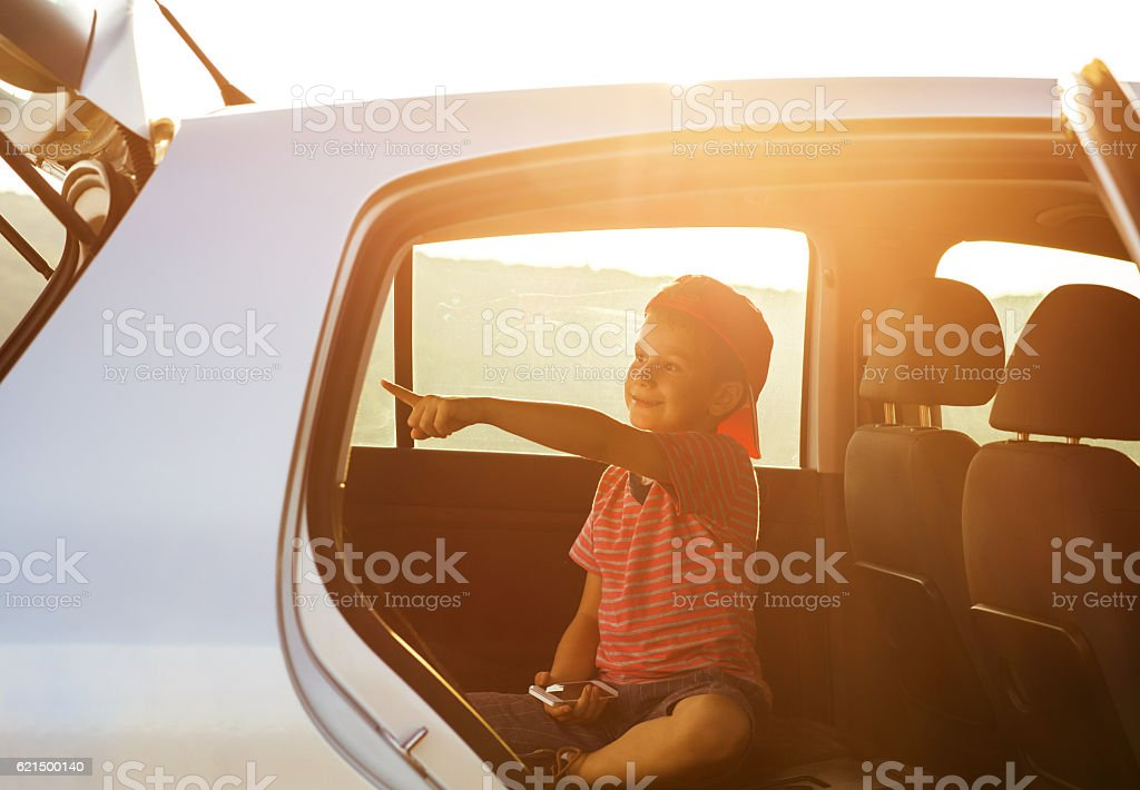 Small boy sitting in the car and pointing at something. Lizenzfreies stock-foto