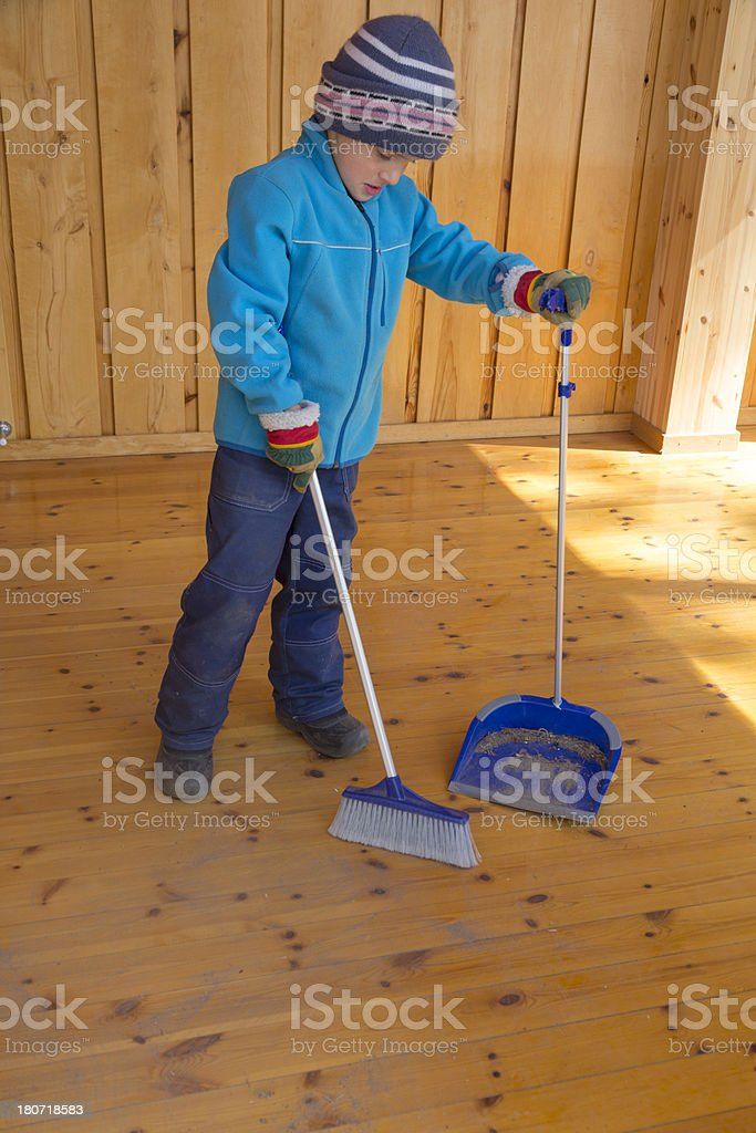 Small boy spring cleaning, sweeping wooden floor. royalty-free stock photo