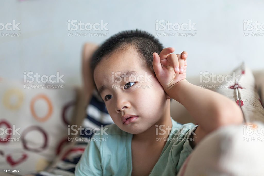 small boy watching TV on sofa stock photo