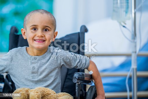 A small boy with hair loss is in a wheelchair in a hospital room. He is smiling at the camera. A stuffed animal is in his lap and an IV drip is beside him.