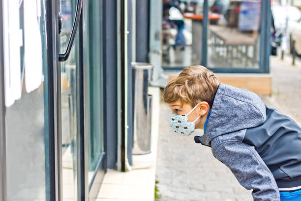 Small boy with face mask looking at store window in the city.
