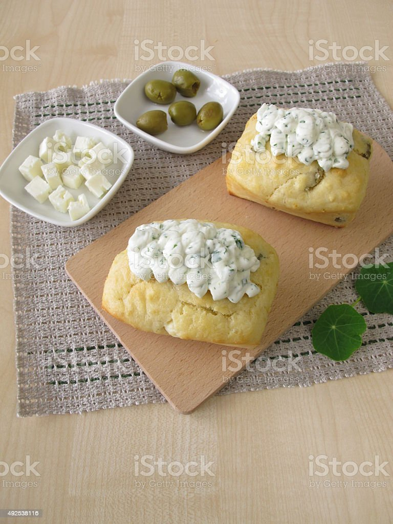 Small breads with olives, feta cheese and herb cheese topping stock photo