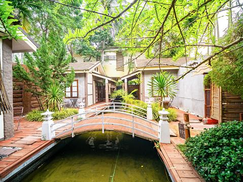 909806032 istock photo Small bridge across pond with tree in resort. 1137884400