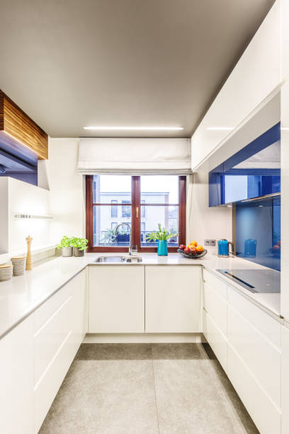 Small bright white kitchen Vertical perspective on a small bright white kitchen interior with a window in the center, elegant countertops and blue modern glass elements narrow stock pictures, royalty-free photos & images