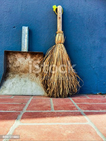 istock Small broom and dustpan on a blue wall background 859731660