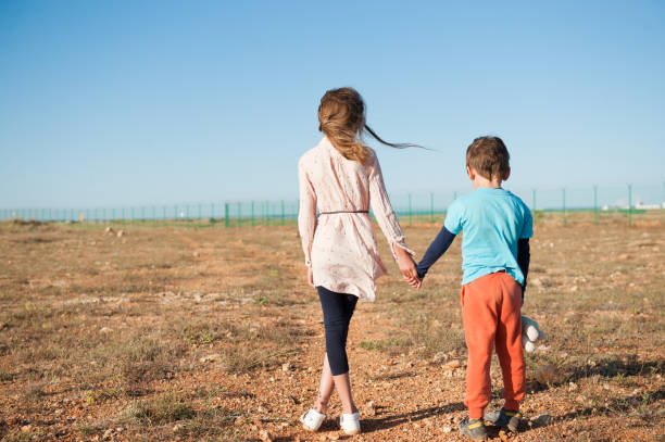 small brother and sister refugees holding hands standing among desert on border small brother and sister refugees holding hands standing among desert on state border deportation stock pictures, royalty-free photos & images