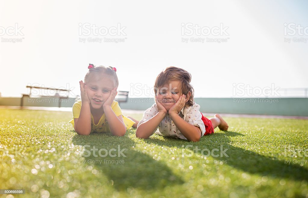 Small brother and sister relaxing together in grass. stock photo