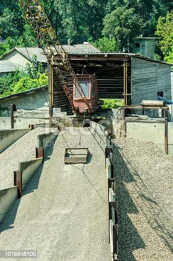 Small bucked loader of gravel stone in pavement industry retro style vertical image