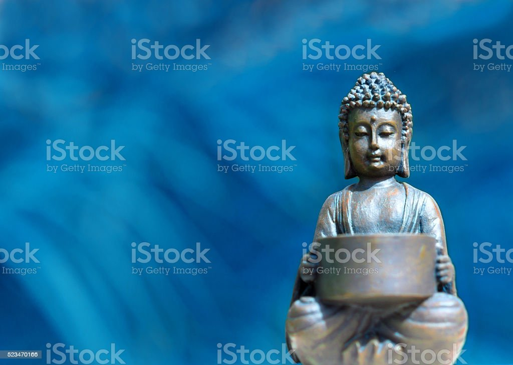 small buddha figurine meditating - in front of blue background stock photo