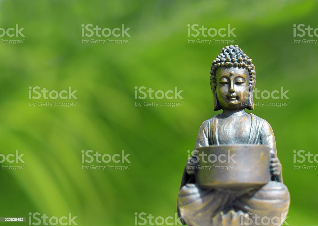 small buddha figurine meditating - in front of green background stock photo