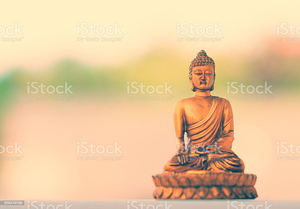small buddha figurine meditating - in front of  white background stock photo