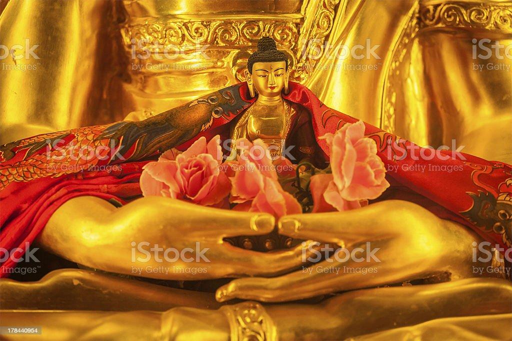 Small Buddha Sakyamuni statue in hands of large stock photo