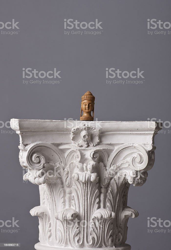small buddha statue on a corinthian capital stock photo