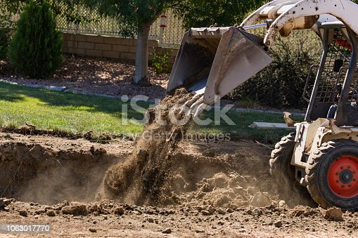 Small Bulldozer Digging In Yard For Pool Installation