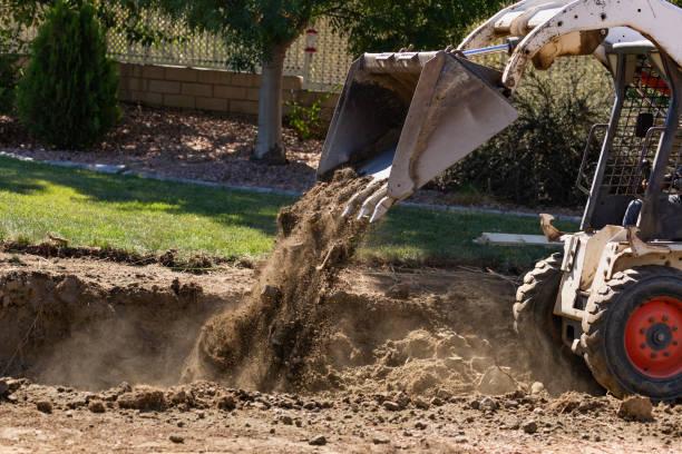 kleine bulldozer graven in de tuin voor de installatie van het zwembad - graven stockfoto's en -beelden