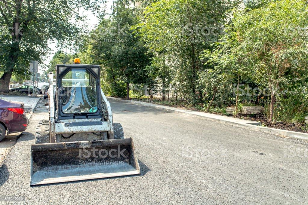 Small bulldozer in city stock photo