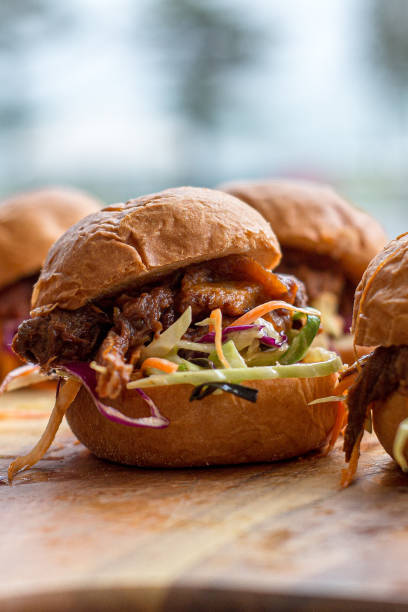 Small burger on a board Small burgers or sliders on a wooden board. Pulled pork with colourful coleslaw in a small bun. Brightly lit in natural light. slider burger stock pictures, royalty-free photos & images