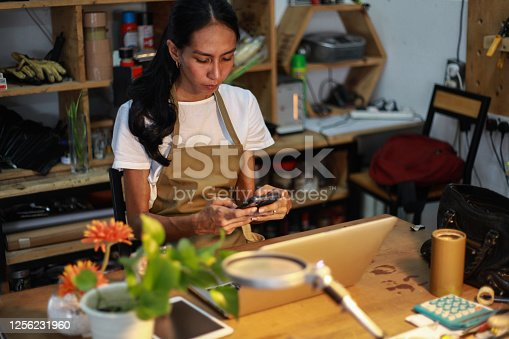 A woman carpenter is using a laptop in her small office / workshop.
