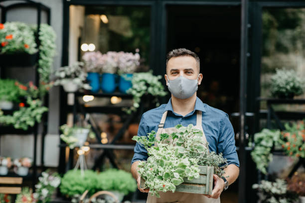 Small business and start of working day. Man in protective mask takes out box of plants outside stock photo