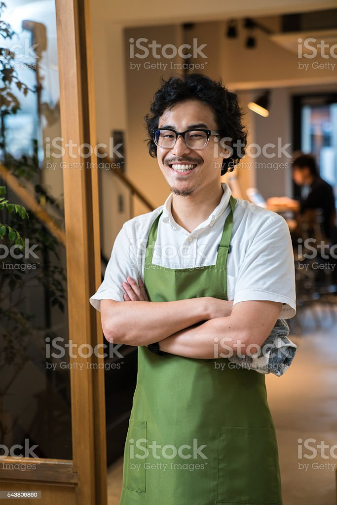 Small business cafe owner greeting customers stock photo