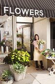 A happy Asian young woman, a Chinese Vietnamese entrepreneur business owner of an urban flower shop. The florist is standing in front of the entrance of the store holding a vase of fresh flowers in her hands, smiling, posing, looking at the camera and celebrating the opening of her business. Photographed in vertical format.