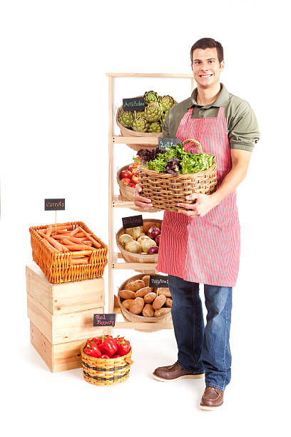 Small Business Local Grocery Store Shop Owner on White Background Subject: Smiling male grocer holding a basket of lettuce as he stands in front of a grocery retail shelf display of vegetables. Isolated on a white background. grocer stock pictures, royalty-free photos & images