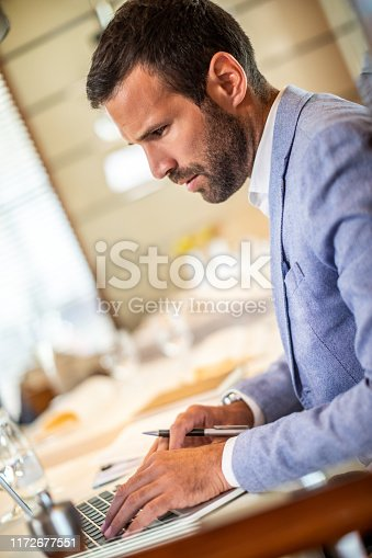 Small business microentrepreneur doing calculations on a laptop while sitting in a restaurant.