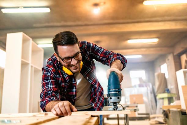 Petite entreprise d'un jeune charpentier dans son atelier de travail - Photo