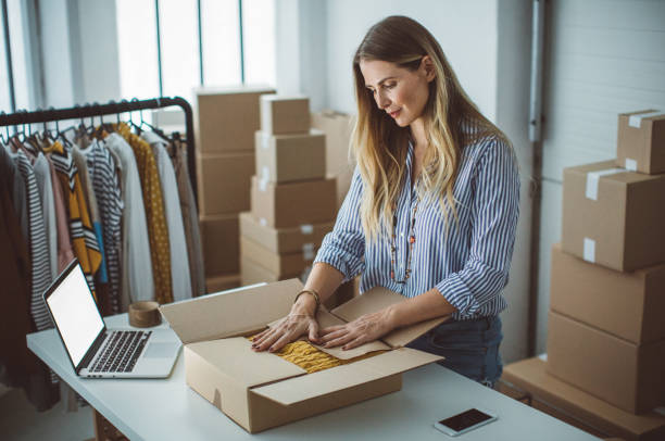 Small business owener Women, owener of small business packing product in boxes, preparing it for delivery. market vendor stock pictures, royalty-free photos & images