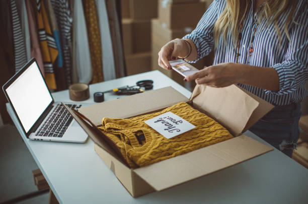 Small business owener Women, owener of small business packing product in boxes, preparing it for delivery. clothes in box stock pictures, royalty-free photos & images